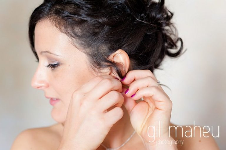 bride putting in earring during bridal preparations at Nantua, Jura wedding by Gill Maheu Photography, photographe de mariage