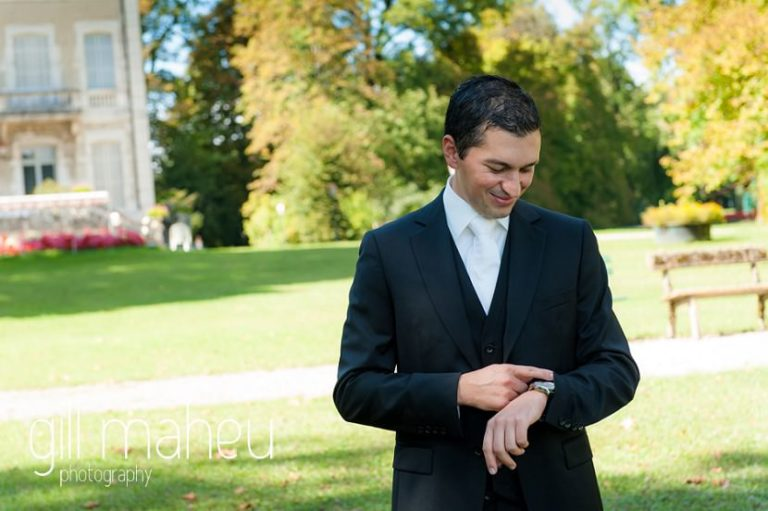 groom looking at his watch whilst waiting for his beautiful bride at first look in front of stunning lake Nantua, Jura wedding by Gill Maheu Photography, photographe de mariag