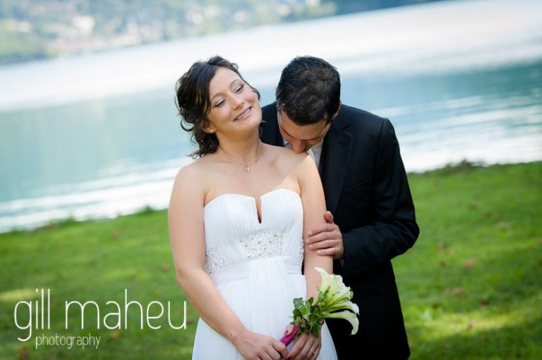groom kissing shoulder of beautiful bride in front of stunning lake Nantua, Jura wedding by Gill Maheu Photography, photographe de mariag