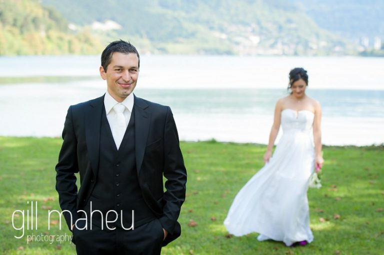 groom waiting for his beautiful bride at first look in front of stunning lake Nantua, Jura wedding by Gill Maheu Photography, photographe de mariage