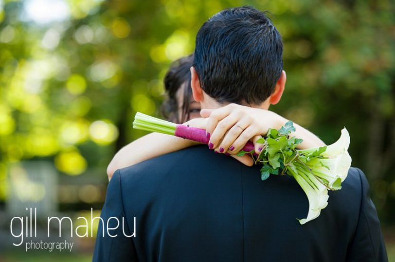 brides hands clasping bouquet around groom's neck at Nantua, Jura wedding by Gill Maheu Photography, photographe de mariage