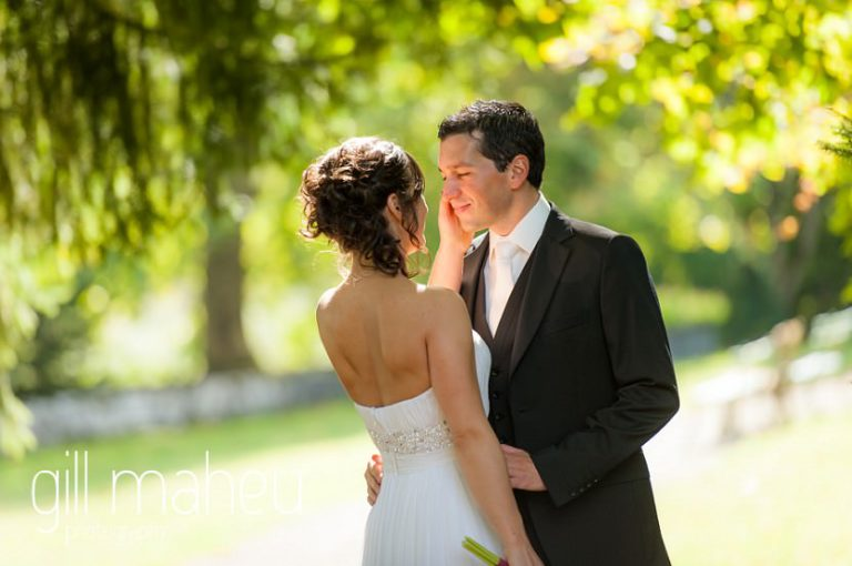 portrait of Groom and bride looking at each other in sunlit gardens at Nantua, Jura wedding by Gill Maheu Photography, photographe de mariage