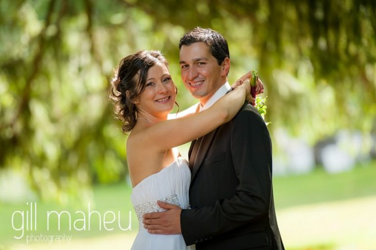 portrait of Groom and bride looking at camera in sunlit gardens at Nantua, Jura wedding by Gill Maheu Photography, photographe de mariage