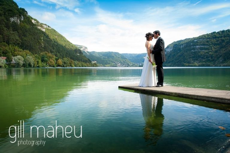 full length portriat of bride and groom on jetty in the lake at Nantua, Jura wedding by Gill Maheu Photography, photographe de mariage
