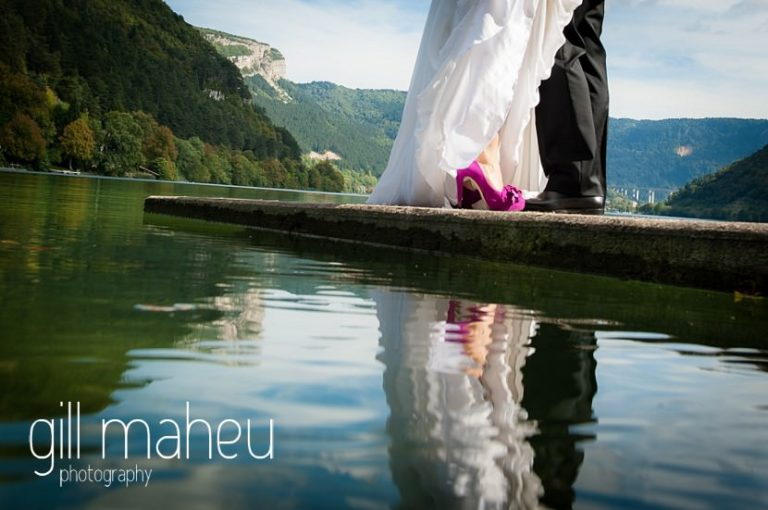 details of fabulous cerise pink marian wedding shoes reflected in the lake at Nantua, Jura wedding by Gill Maheu Photography, photographe de mariage