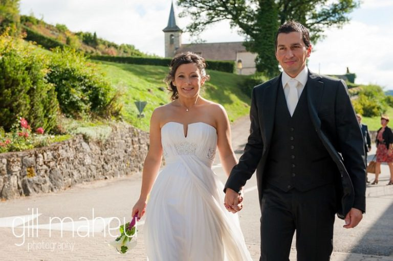 bride and groom walking towards camera after church ceremony at Nantua, Jura wedding by Gill Maheu Photography, photographe de mariage