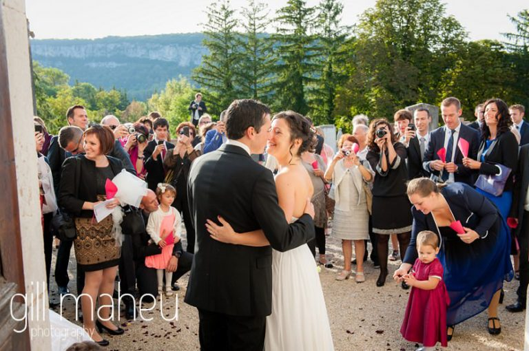 bride and groom kissing under red rose petal confetti after ceremonie at Nantua, Jura wedding by Gill Maheu Photography, photographe de mariage