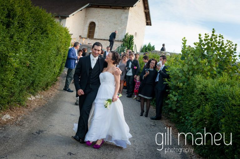 bride and groom walking away from church with celebrating congregation behind them at Nantua, Jura wedding by Gill Maheu Photography, photographe de mariage