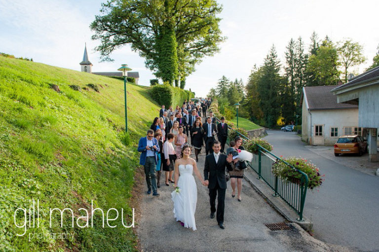 bride and groom walking away from church with celebrating congregation behind them after ceremonie at Nantua, Jura wedding by Gill Maheu Photography, photographe de mariage