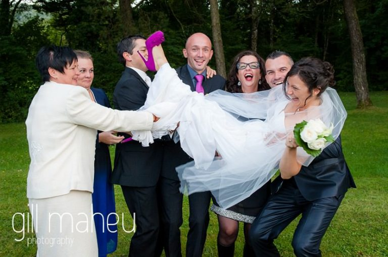 bride in the arms of groom and groomsmen during group shots at Nantua, Jura wedding by Gill Maheu Photography, photographe de mariage