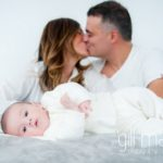 portrait of new baby in foreground and parents kissing in the background at new baby new family portrait session in Aix les Bains by Gill Maheu Photography, photographe de bébé et famille