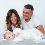 portrait of new baby in foreground and parents looking at him in the background at new baby new family portrait session in Aix les Bains by Gill Maheu Photography, photographe de bébé et famille