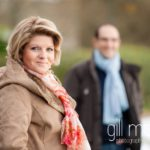 bride to be in foreground with groom in background in the winter sunshine in Talloires, Annecy by Gill Maheu Photography, photographe de mariage