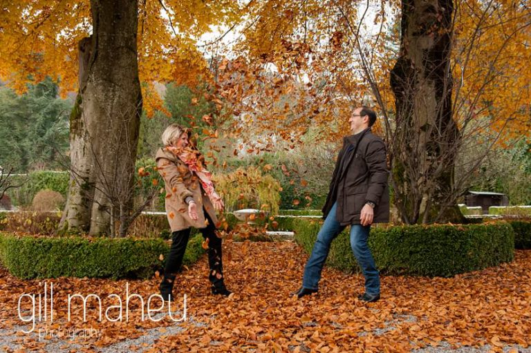 engaged couple having a fallen leaf battle in the gardens of the Abbaye de Talloires, Annecy by Gill Maheu Photography, photographe de mariage