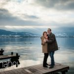 full length shot of engaged couple laughing together in the winter sunshine against the lake in Talloires, Annecy by Gill Maheu Photography, photographe de mariage