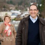 portrait of very happy groom to be with fiancé in background in the winter sunshine in Talloires, Annecy by Gill Maheu Photography, photographe de mariage