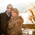 portrait of engaged couple embracing in the winter sunshine in Talloires, Annecy by Gill Maheu Photography, photographe de mariage