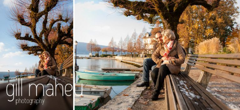 wide angle shot of engaged couple sitting on a bench lookig at the Lake in the winter sunshine in Talloires, Annecy by Gill Maheu Photography, photographe de mariage
