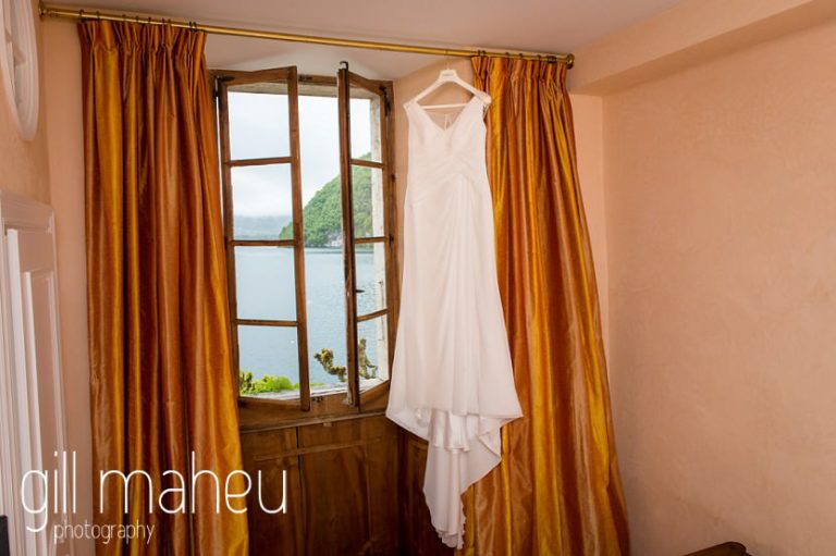beautiful sequinned Pronovias wedding dress hanging in window frame at Abbaye de Talloires, Annecy wedding by Gill Maheu Photography, photographe de mariage