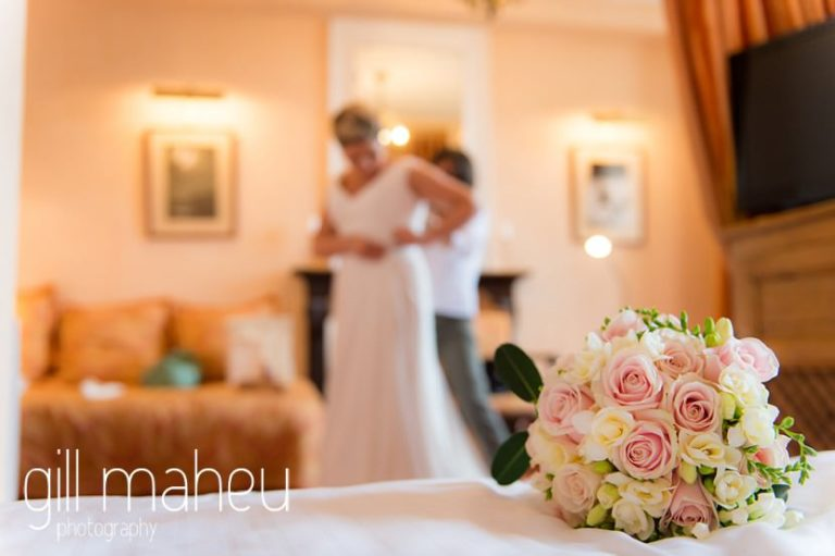 beuatiful bride being helped into her sequinned Pronovias wedding dress by her mum at Abbaye de Talloires, Annecy wedding by Gill Maheu Photography, photographe de mariage