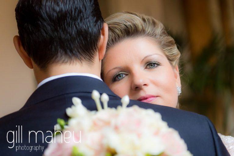 bride peeking over grooms shoulders at Abbaye de Talloires, Annecy wedding by Gill Maheu Photography, photographe de mariage