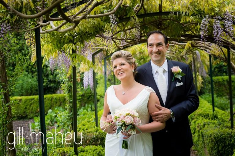 bride and groom laughing under the wisteria arch in the gardens of the Abbaye de Talloires, Annecy wedding by Gill Maheu Photography, photographe de mariage