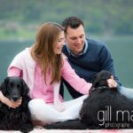 portrait of engaged couple with their dogs on jetty in front of Talloires, Annecy engagement session by Gill Maheu Photography, photographe de mariage
