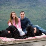 portrait of engaged couple with their dogs on jetty in Lake Annecy opposite Talloires engagement session by Gill Maheu Photography, photographe de mariage
