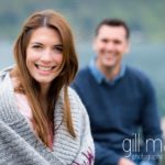close up portrait of bride with groom in background groom laughing on jetty in Lake Annecy opposite Talloires, engagement session by Gill Maheu Photography, photographe de mariage