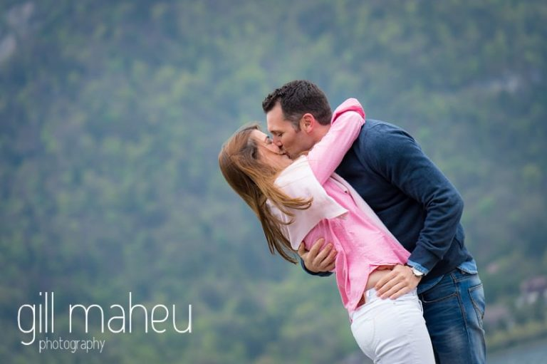 romantic portrait of bride and groom kissing on jetty in Lake Annecy opposite Talloires, engagement session by Gill Maheu Photography, photographe de mariage