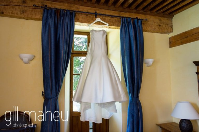 stunning Pronovias wedding dress hanging in the window of the Abbaye de Talloires, Annecy wedding by Gill Maheu Photography, photographe de mariage