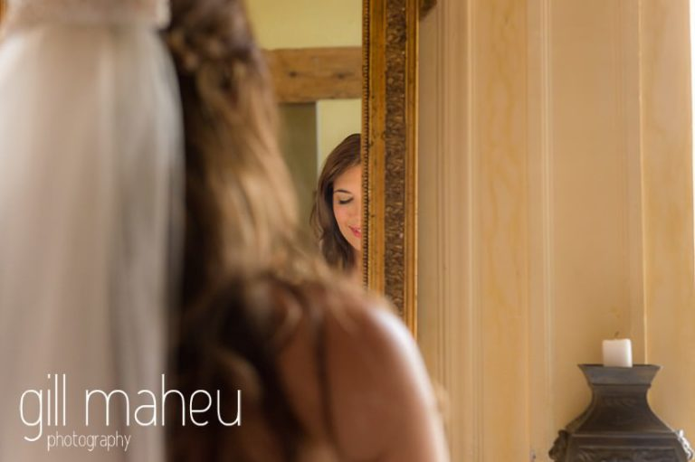 bride looking in mirror just before leaving for wedding ceremony in the gardens of the Abbaye de Talloires, Annecy wedding by Gill Maheu Photography, photographe de mariage