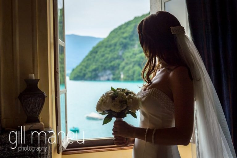 bride silhouetted against view of lake annecy from bridal suite at Abbaye de Talloires, Annecy wedding by Gill Maheu Photography, photographe de mariage