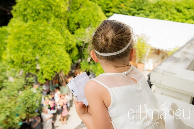 adorable little bridesmaid gazing down on guests gathering in the gardens from bridal suite at Abbaye de Talloires, Annecy wedding by Gill Maheu Photography, photographe de mariage