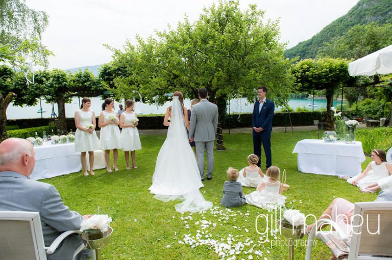 photo from aisle of the wedding ceremony with the flower girls sitting on the grass in the gardens of the Abbaye de Talloires, Annecy wedding by Gill Maheu Photography, photographe de mariage