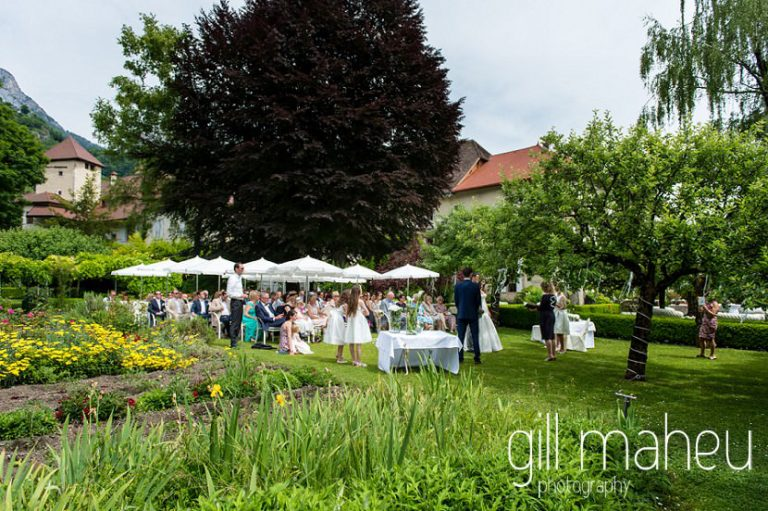 wide angle shot of wedding ceremony showing wedding couple and all guest in front of the backdrop of the Abbaye de Talloires, Annecy wedding by Gill Maheu Photography, photographe de mariage