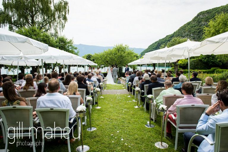 photograph of wedding ceremony taken from back of the congegration in the gardens of Abbaye de Talloires, Annecy wedding by Gill Maheu Photography, photographe de mariage