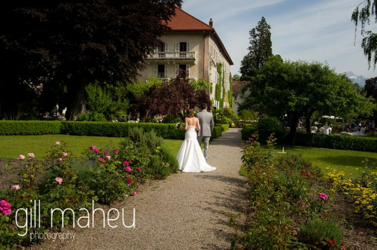 happy couple walking away from camera towards vin d'honneur cocktail outside the Abbaye de Talloires, Annecy wedding by Gill Maheu Photography, photographe de mariage