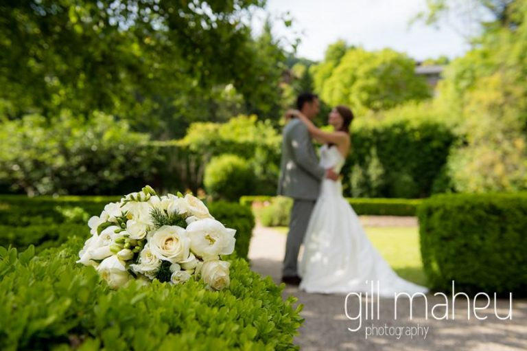 close up of wedding bouquet on clipped hedge with couple kissing in the background at Abbaye de Talloires, Annecy wedding by Gill Maheu Photography, photographe de mariage