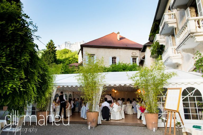 wide angle shot from distance of guests enjoying dinner in the marquee at Abbaye de Talloires, Annecy wedding by Gill Maheu Photography, photographe de mariage