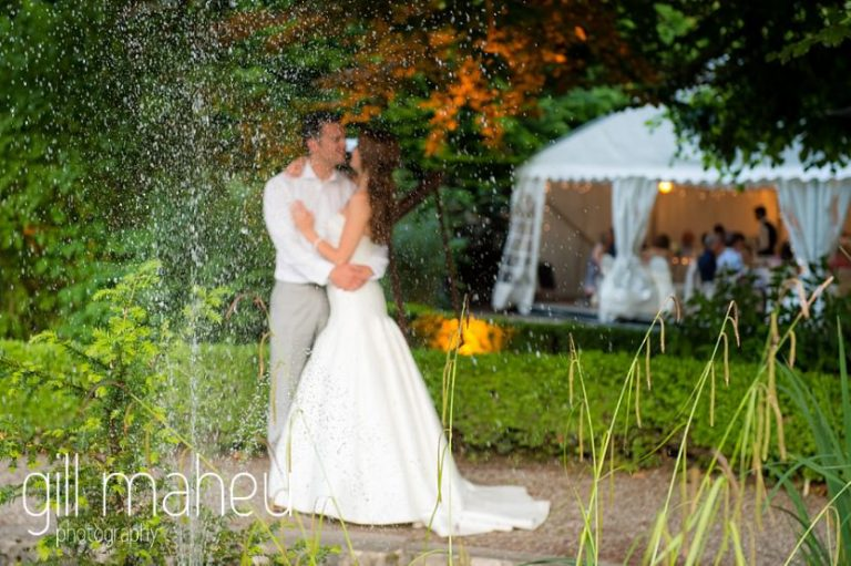 romantic photo through fountain of bride and groom embracing in the gardens of the Abbaye de Talloires, Annecy wedding by Gill Maheu Photography, photographe de mariage