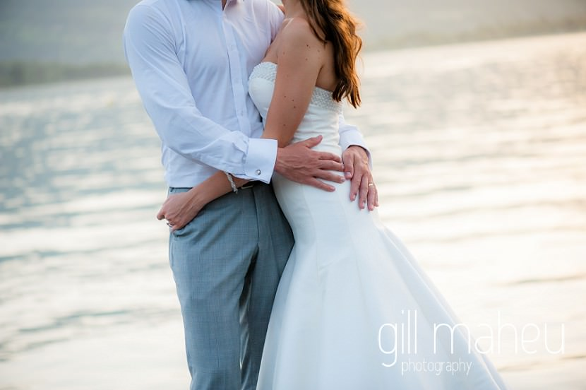 romantic close up shot of bride and groom with their arms around each other in front of the lake at Abbaye de Talloires, Annecy wedding by Gill Maheu Photography, photographe de mariage