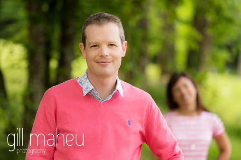 portrait of groom to be with bride in background on Golf du Lac d'Annecy, Talloires engagement session by Gill Maheu Photography, photographe de mariage
