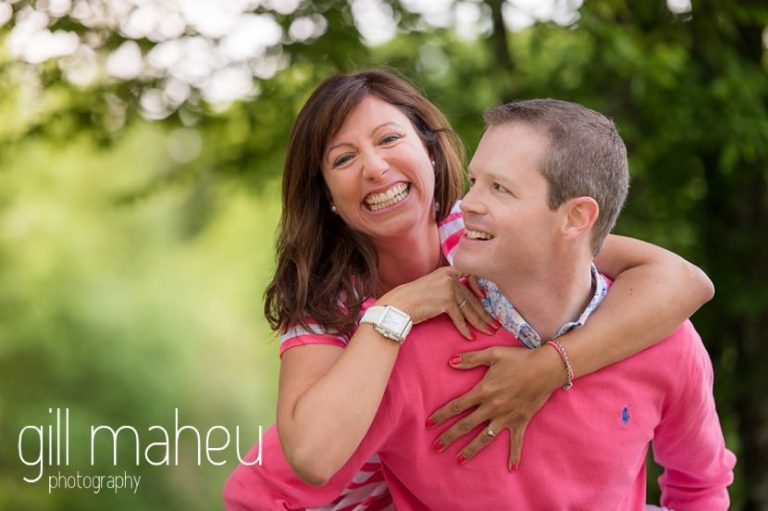 seriously happy engaged couple in pink on Golf du Lac d'Annecy, Talloires engagement session by Gill Maheu Photography, photographe de mariage