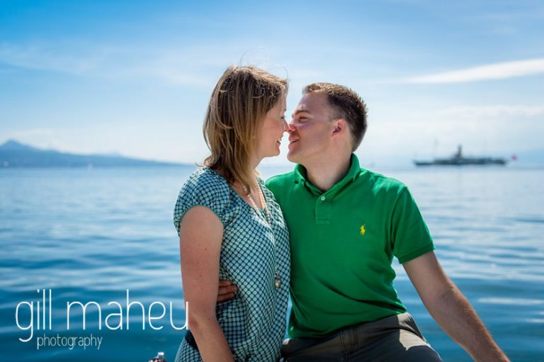 bride kissing groom on speed boat on Lac Léman with CGN bateau Belle Epoque in the background , Lausanne engagement session by Gill Maheu Photography, photographe de mariage