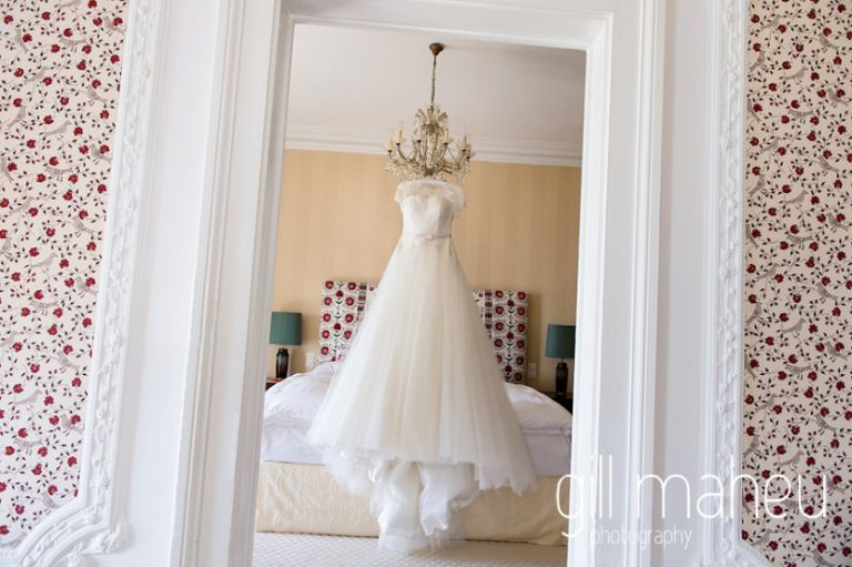 stunning Lusan Madongus white lace wedding dress hanging from chandelier at luxury hotel Trois Couronnes, Vevey, Lake Geneva wedding by Gill Maheu Photography, photographe de mariage