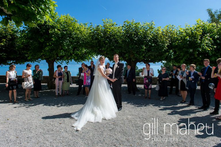 bride and groom leaving wedding ceremony in Lutry under bubble confetti before hotel Trois Couronnes, Vevey, Lake Geneva wedding by Gill Maheu Photography, photographe de mariage
