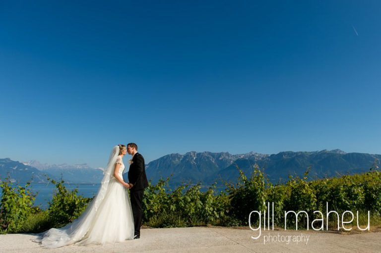 full length portrait of wedding couple in vineyards with stunning view of Lac Leman before luxury hotel Trois Couronnes, Vevey, Lake Geneva wedding by Gill Maheu Photography, photographe de mariage