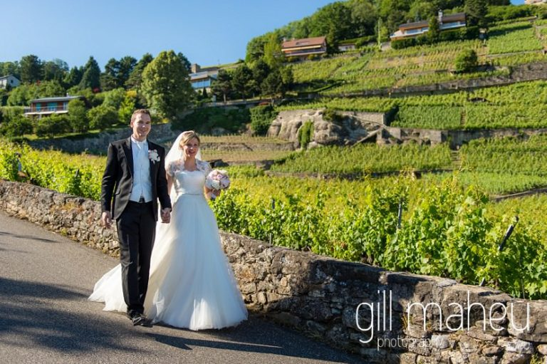 portrait of wedding couple walking through vineyards in front of stunning view of Lac Leman before luxury hotel Trois Couronnes, Vevey, Lake Geneva wedding by Gill Maheu Photography, photographe de mariage