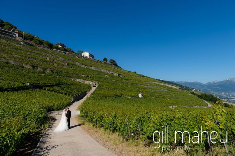 wide angle shot of portrait of wedding couple walking through vineyards in front of stunning view of Lac Leman before luxury hotel Trois Couronnes, Vevey, Lake Geneva wedding by Gill Maheu Photography, photographe de mariage